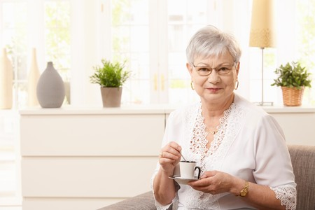 Senior woman drinking coffee in living room, looking at camera smiling. photo