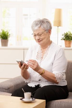 Senior woman sitting on sofa, using palmtop, smiling. photo