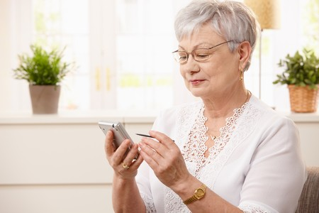 Portrait of modern senior woman using pda at home, smiling. photo
