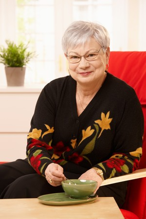 Senior woman drinking tea, sitting in armchair, looking at camera, smiling. Stock Photo - 7217333