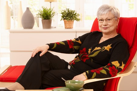 Senior woman relaxing at home, sitting in armchair, having tea. Stock Photo - 7217332