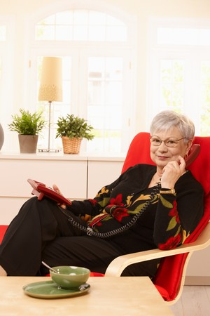 Pensioner lady using landline phone, sitting in armchair, smiling. Stock Photo - 7217277