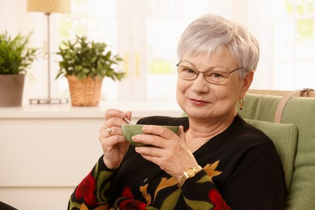 Portrait of senior lady drinking tea at home, holding cup, looking at camera, smiling . photo