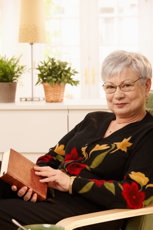 Smiling elderly woman sitting in armchair holding book, looking at camera. Stock Photo - 7217305