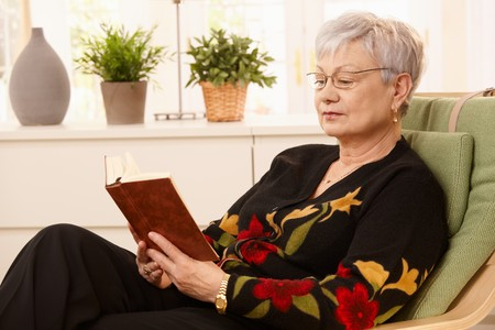 Portrait of pensioner reading in armchair in bright living room. Stock Photo - 7217374