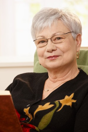 Closeup portrait of senior woman with book, looking at camera, smiling. photo