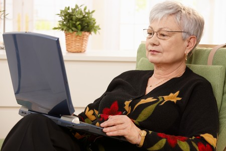 Senior woman using laptop computer at home, sitting in armchair. photo