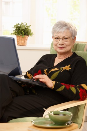 Portrait of modern pensioner woman using laptop computer at home, smiling. Stock Photo - 7217291