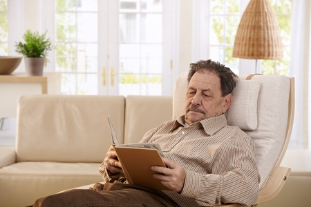 Senior man resting in chair at home, reading book. Stock Photo - 7250522
