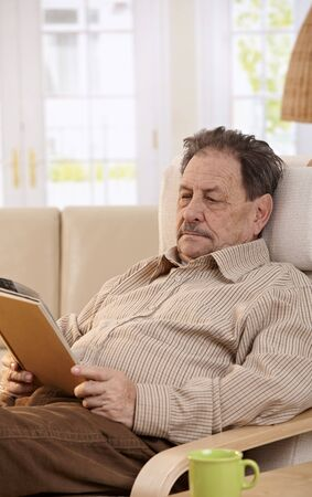 Senior man resting in chair at home, reading book. Stock Photo - 7249280
