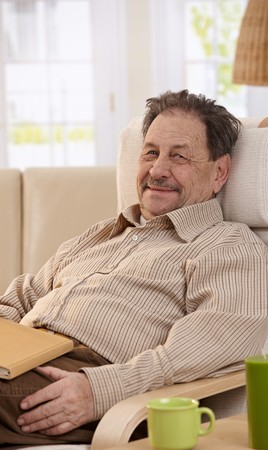Senior man resting in chair at home, reading book. Looking at camera, smiling. photo