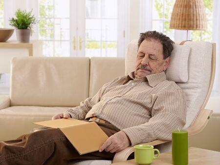 asleep chair: Senior man sleeping in armchair at home. Stock Photo