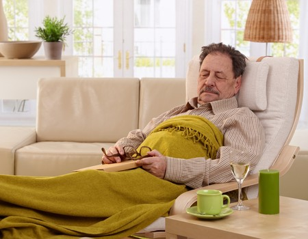 tired face: Senior man napping in armchair at home. Stock Photo