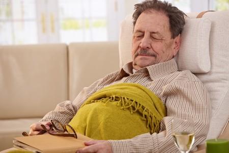 hombre sentado: Hombre Senior mentir en el sill�n, se qued� dormido mientras lee el libro.