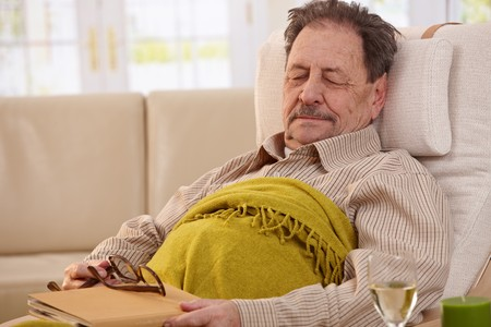 one mature man only: Senior man lying in armchair, fell asleep while reading book. Stock Photo