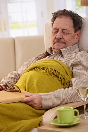 napping: Senior man lying in armchair at home, sleeping in afternoon sunlight. Stock Photo