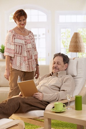 Senior man resting in armchair at home, reading book, his wife standing beside. photo