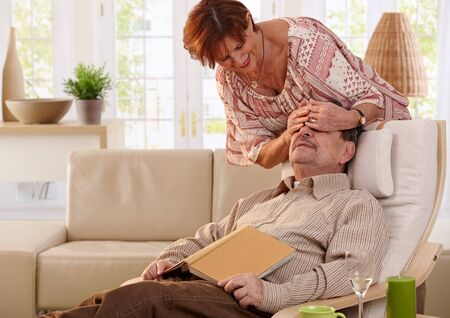 Senior woman surprising husband sitting in armchair with book in hand. photo