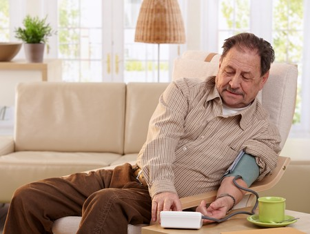 Old man sitting in armchair at home, measuring his blood pressure, smiling.  Stock Photo - 7249277