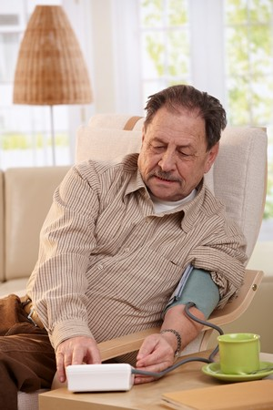 Old man sitting in armchair at home, measuring his blood pressure.