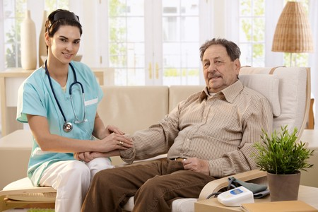 Nurse measuring blood pressure of senior man at home. Smiling to each other. Stock Photo - 7249284