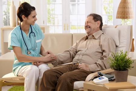 buena salud: Enfermera de medici�n de la presi�n arterial del hombre senior en casa. Sonriendo entre s�.  Foto de archivo
