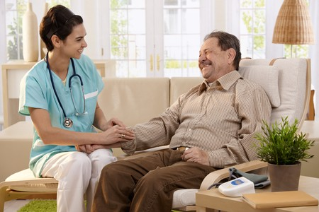 home health care: Nurse measuring blood pressure of senior man at home. Smiling to each other. Stock Photo