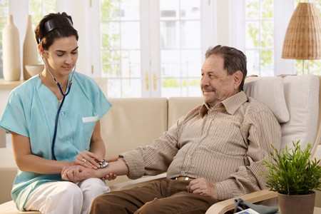 Nurse using stethoscope and measuring blood pressure of senior man at home.  Stock Photo - 7249295