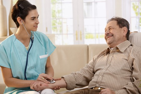 Female physician using stethoscope and measuring blood pressure of senior man at home. Stock Photo - 7249306