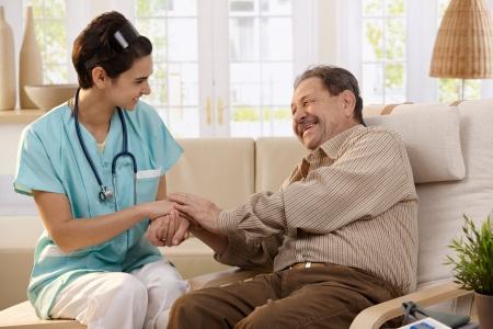 enfermeras: Feliz enfermera mano de sesi�n de pacientes ancianos lado a lado en el hogar, riendo.  Foto de archivo
