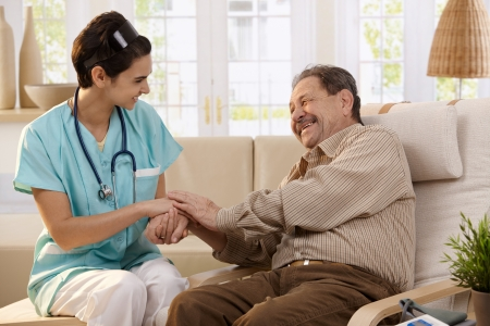 Happy nurse holding hands of elderly patient sitting side by side at home, laughing. photo