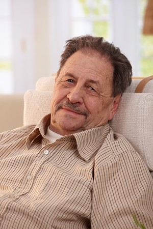 Portrait of senior man resting in armchair at home, looking at camera. Stock Photo - 7249310