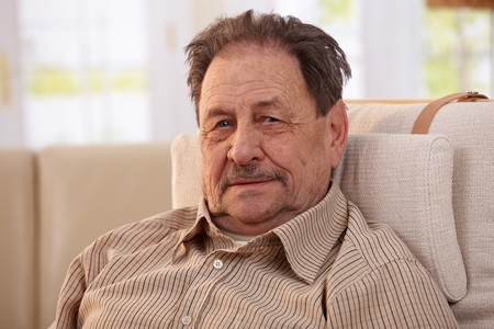 Portrait of senior man resting in armchair at home, looking at camera. Stock Photo - 7249312