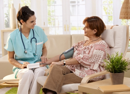 home health care: Nurse measuring blood pressure of senior woman at home. Smiling to each other.