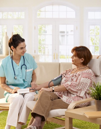 at each other: Nurse measuring blood pressure of senior woman at home. Smiling to each other.