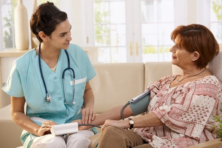 Nurse measuring blood pressure of senior woman at home. Smiling to each other. photo