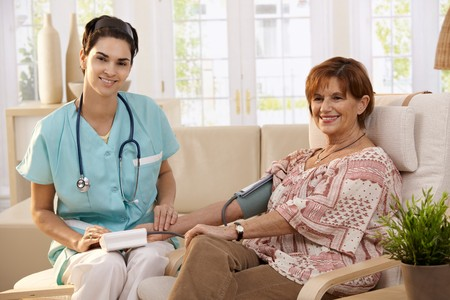 Female doctor measuring blood pressure of senior woman at home. Looking at camera, smiling. Stock Photo - 7217420