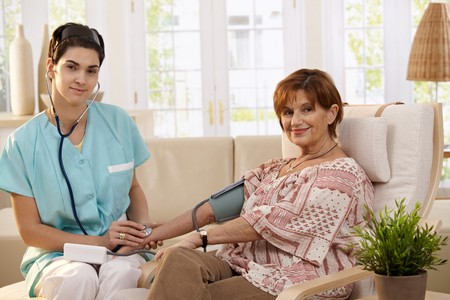 Female physician using stethoscope and measuring blood pressure of senior woman at home.  photo