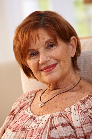 Portrait of attractive elderly woman sitting in chair at home looking at camera smiling. photo