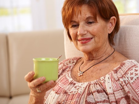 Portrait of happy elderly woman sitting in chair at home, holding coffee cup, smiling. photo