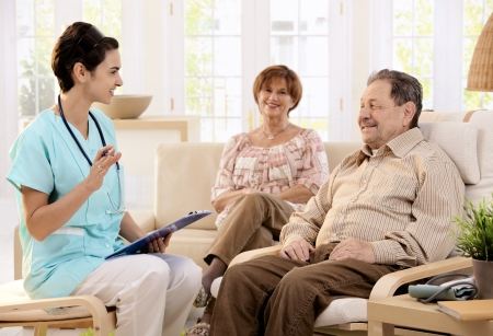 home care nurse: Nurse talking with elderly people and making notes during examination at home, smiling. Stock Photo