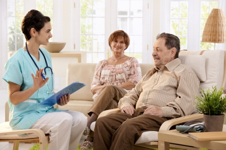 health drink: Nurse talking with elderly people and making notes during examination at home, smiling. Stock Photo