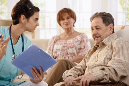 ヘルスケア: 看護師の自宅でルーチン検査中にテスト結果を示す高齢者と話しています。 写真素材