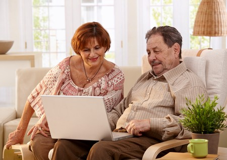 Elderly couple using laptop computer at home, looking at screen, smiling. photo