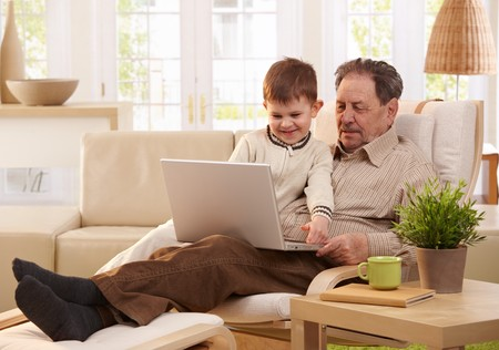 Grandfather and grandson sitting in armchair and using computer together, smiling.   photo