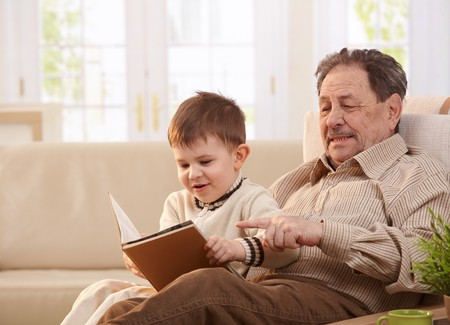 photo story: Grandfather sitting in armchair at home, holding his grandson who looking pictures in book.