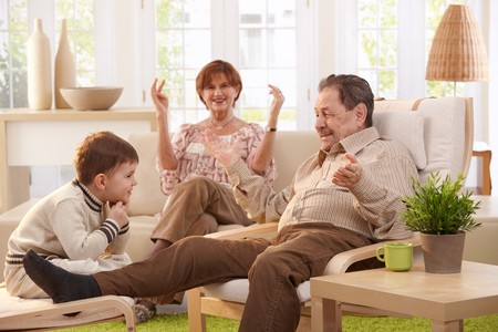 Grandparents with grandson sitting in living room at home having fun together. photo