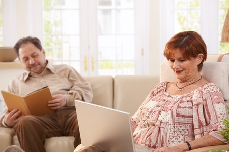 Senior couple resting at home reading book and browsing internet on laptop computer. photo