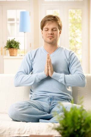 Handsome young man doing yoga meditation at home, sitting in living room. photo