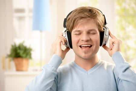 Happy young man listening to music on headphones with eyes closed, smiling. Stock Photo - 7249381